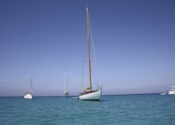Classic sailing yacht Yanira anchored off beach